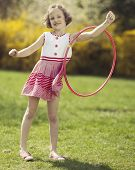 Young girl using hula hoop on arm in a park