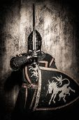 Medieval knight  holding sword in front of his face