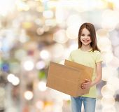 advertising, childhood, delivery, mail and people - smiling little girl holding open cardboard box over holidays background