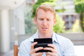 picture of pissed off  - Closeup portrait annoyed young man in blue shirt pissed off by what he heard or sees on his cell phone isolated outdoors outside background - JPG