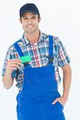 Portrait of confident plumber showing green card over white background