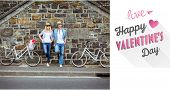 Hip young couple standing by brick wall with their bikes against cute valentines message