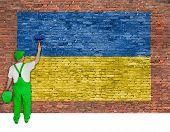 House Painter Paints Flag Of Ukraine On Brick Wall