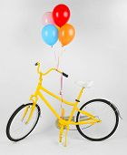 Yellow bicycle with balloons isolated on white