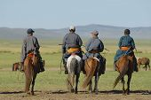 Men ride on horseback, circa Harhorin Mongolia.