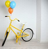 Yellow bicycle with balloons on brick wall background