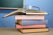Stack of books with glasses on wooden desk, on colorful wall and blackboard background