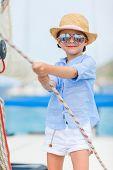 Adorable little girl enjoying sailing on a luxury catamaran or yacht