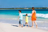 Mother and kids on a Caribbean vacation walking along a beach