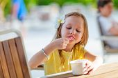 Adorable little girl eating ice cream