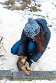 Happy girl playing with puppy in winter outdoors.