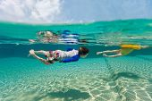 Split above and underwater photo of adorable kids having fun swimming at pool on summer vacation