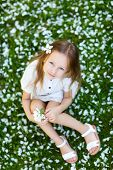 Adorable little girl on a grass covered with white flower petals on spring day