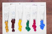 Colorful paint tubes squeezed on white sheet of paper and wooden table background