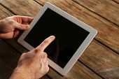 Hands holding tablet PC on wooden table background