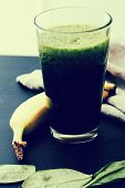 Spinach drink and banana on a wooden table