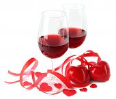 Composition with red wine in glasses, red roses, ribbon and decorative hearts isolated on white