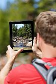 Hiking hiker man taking pictures of forest on digital tablet computer. Young adult doing mobile photography of nature landscape in Yosemite National Park, California, USA.