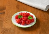 plate of fresh raspberries, on the wooden table