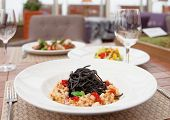 Black squid ink pasta with seafood and other dishes on restaurant table