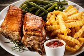 Grilled pork ribs, chips and vegetables