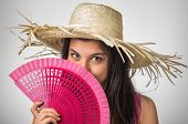 Pretty young lady with blue eyes wearing a straw hat and a pink fan