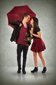 Young couple in love with red umbrella and flower over textured background