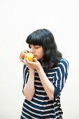 Brunette Girl Smells Apple And Orange In Her Hands
