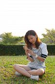 woman and smart phone on green grass field