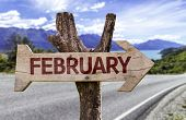 February wooden sign with a road on background