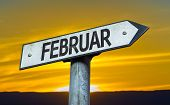 February (in German) sign with a sunset background