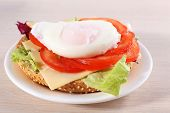 Sandwich with poached egg and vegetables on plate on wooden background