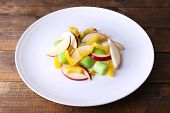 Waldorf salad with salad pepper on plate on wooden background