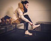 Girl putting on skates  in locker room