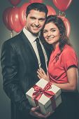 Happy couple with balloons and gift box