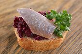 Herring with beets on rye toast on wooden background