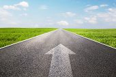foto of arrow  - Arrow sign pointing forward on long empty straight road - JPG