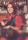 Beautiful redhead barmaid with cocktail behind bar counter