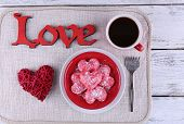 Romantic still life with cookies in form of heart on color wooden planks background