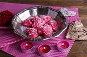 Cookies in form of heart on metal tray with candles and napkins on rustic wooden table background