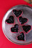 Cookies in form of heart covered chocolate on metal tray with napkin on wooden table background