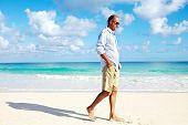 Handsome man walking on sandy beach. Vacation