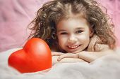 little girl holding a heart