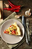 Piece of vegetable pie with paprika, tomatoes and cheese on plate, on wooden background