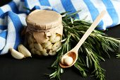 Canned garlic in glass jar and wicker mat and rosemary branches, on dark wooden background