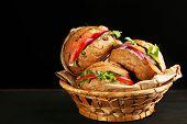 Sandwiches with salmon in wicker basket, on dark background