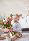 Adorable child with bunch of flowers sitting on the floor
