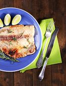 foto of pangasius  - Dish of Pangasius fillet with rosemary and lime on wooden table background - JPG