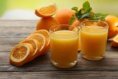 Glass of orange juice and slices on wooden table and bright background