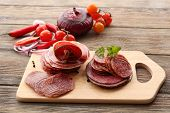 Sliced salami with chili pepper, cherry tomatoes, onion and spices on cutting board and wooden table background